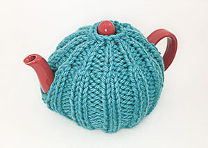 red teapot covered in ribbed teal tea cozy