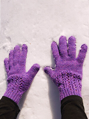 purple knit gloves iwth lace detail on back of hands, shown on snowy background