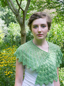 Young woman wearing green lacy shawl with a background of yellow flowers