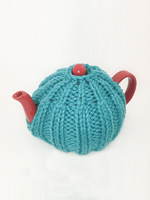 teal ribbed patterned tea cozy on red teapot