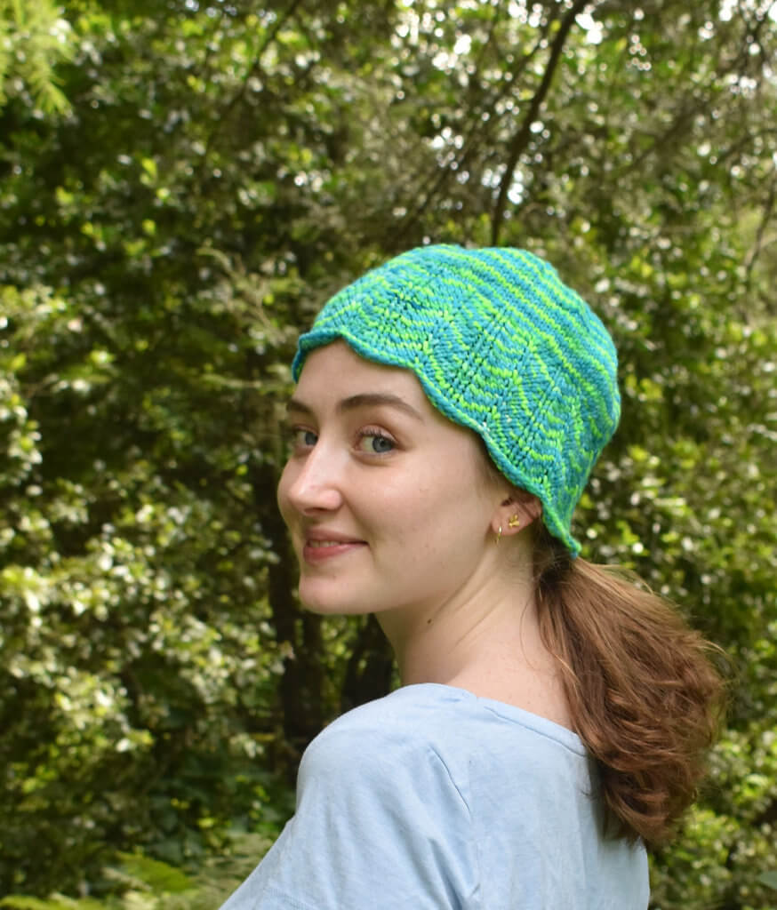Bright green and blue hat worn on a smiling girl
