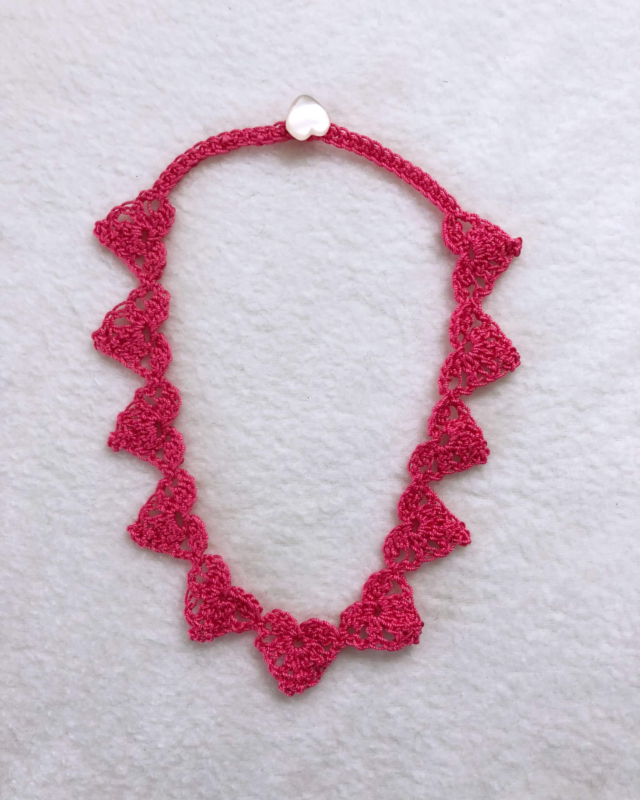 Pink Thread Crochet Heart Necklace on white background