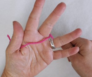 How to wind a yarn butterfly Step 1: Hold yarn tail under thumb.