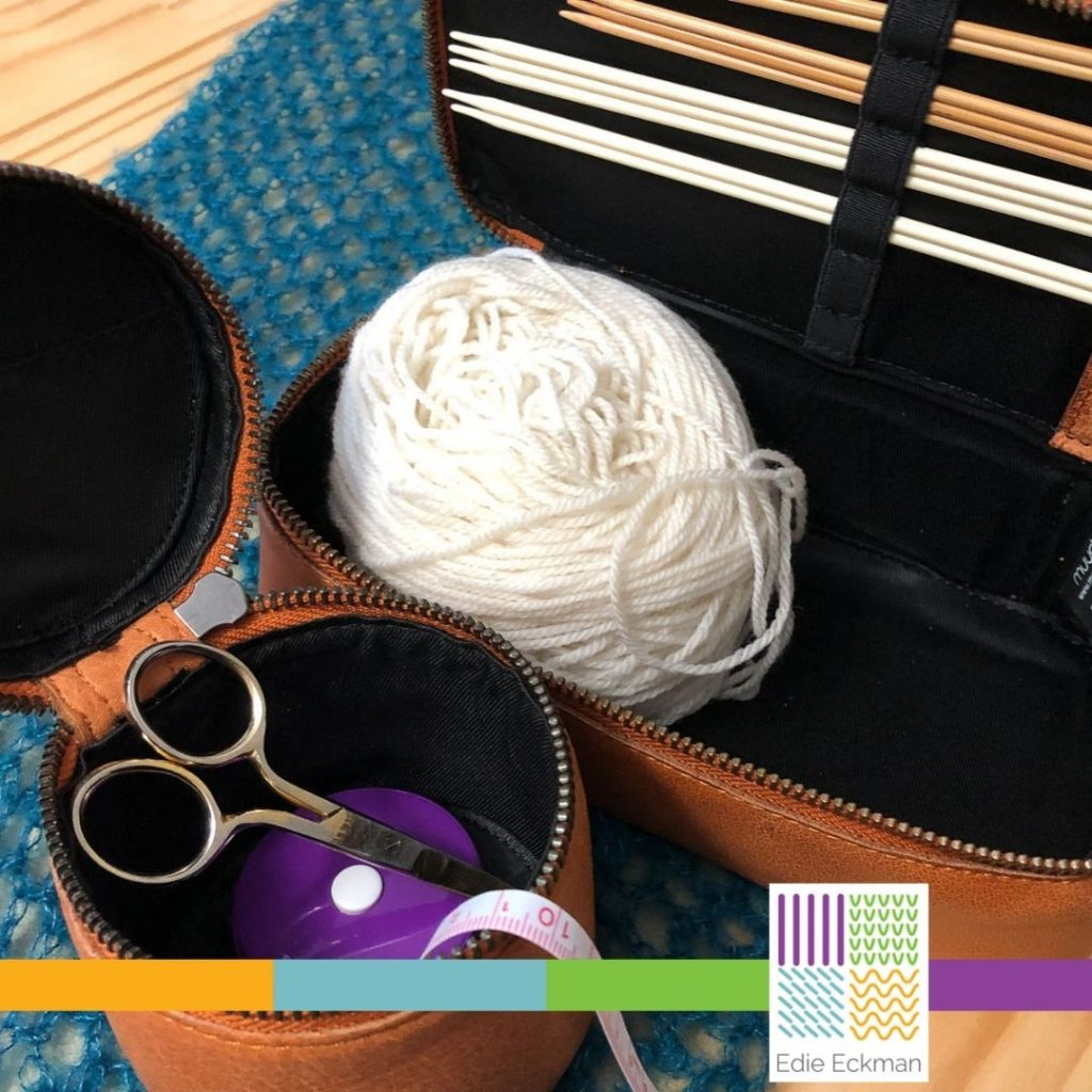 two open zippered leather boxes, holding knitting needles, a ball of yarn, scissors and tape measure