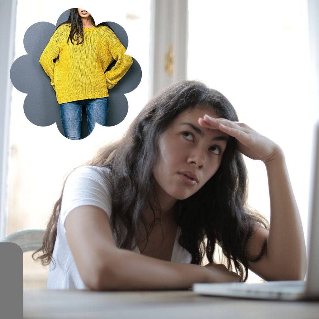 young woman at computer thinking of a bright yellow sweater (in a thought bubble)