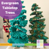 two crocheted trees with a felted snowman in the background