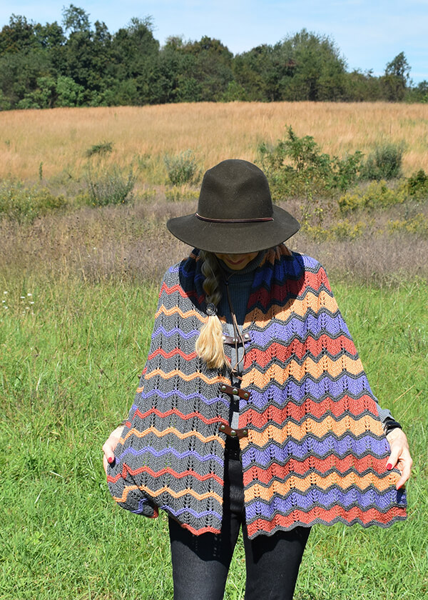 grey/purple/orange/gold chevron-patterned poncho worn on a woman