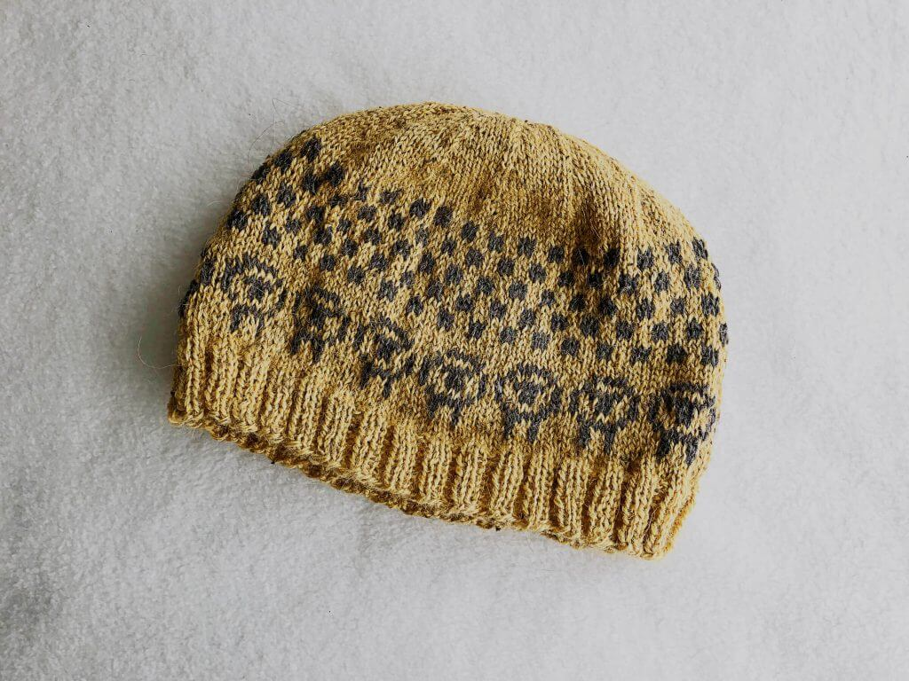 Golden hat with grey sheep and checked pattern