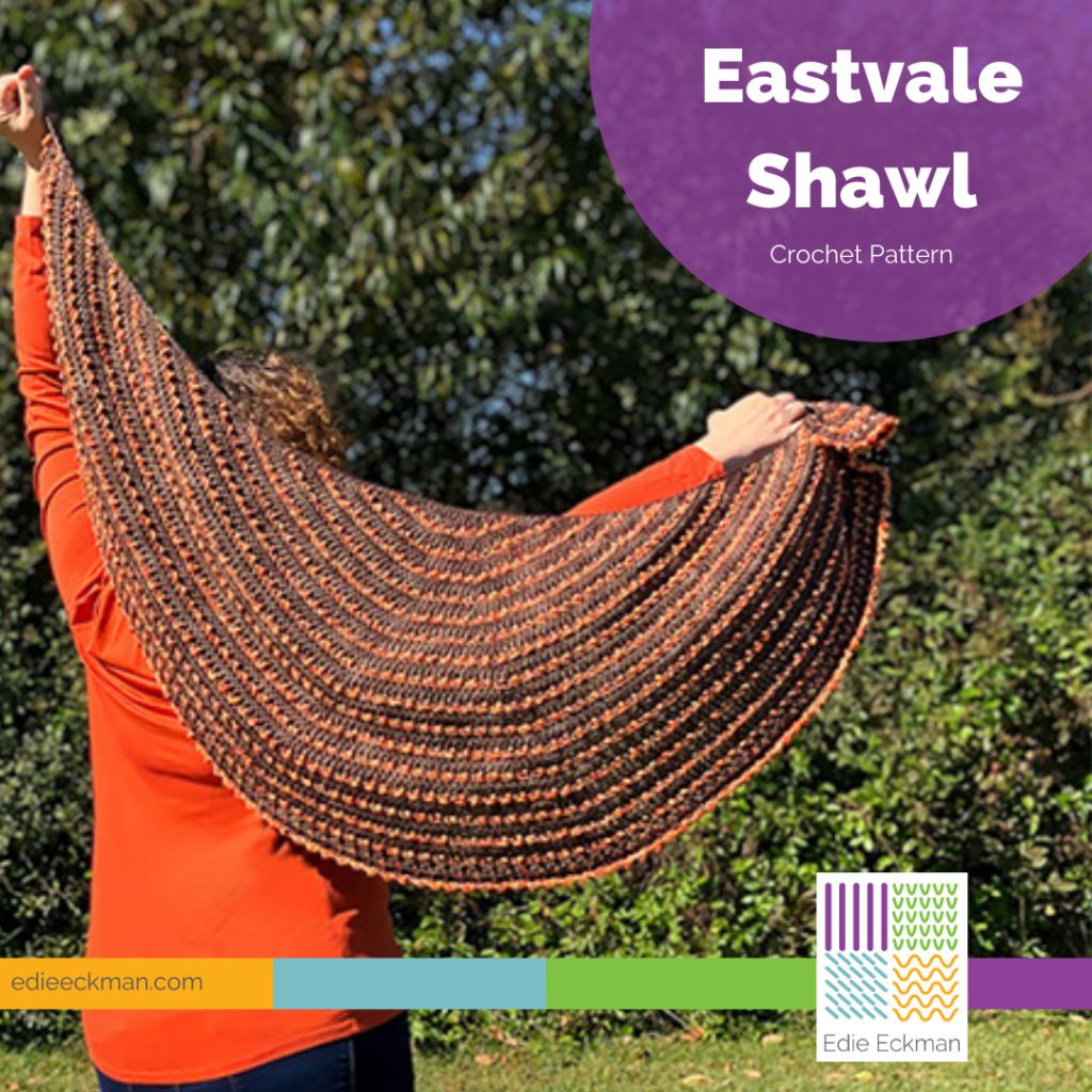 Brown crescent shaped shawl with orange accents stretched out
