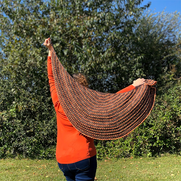 brown and orange crescent shaped shawl held out