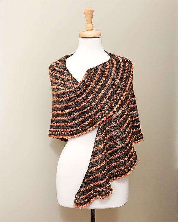 brown shawl with textured orange stripes on dress form