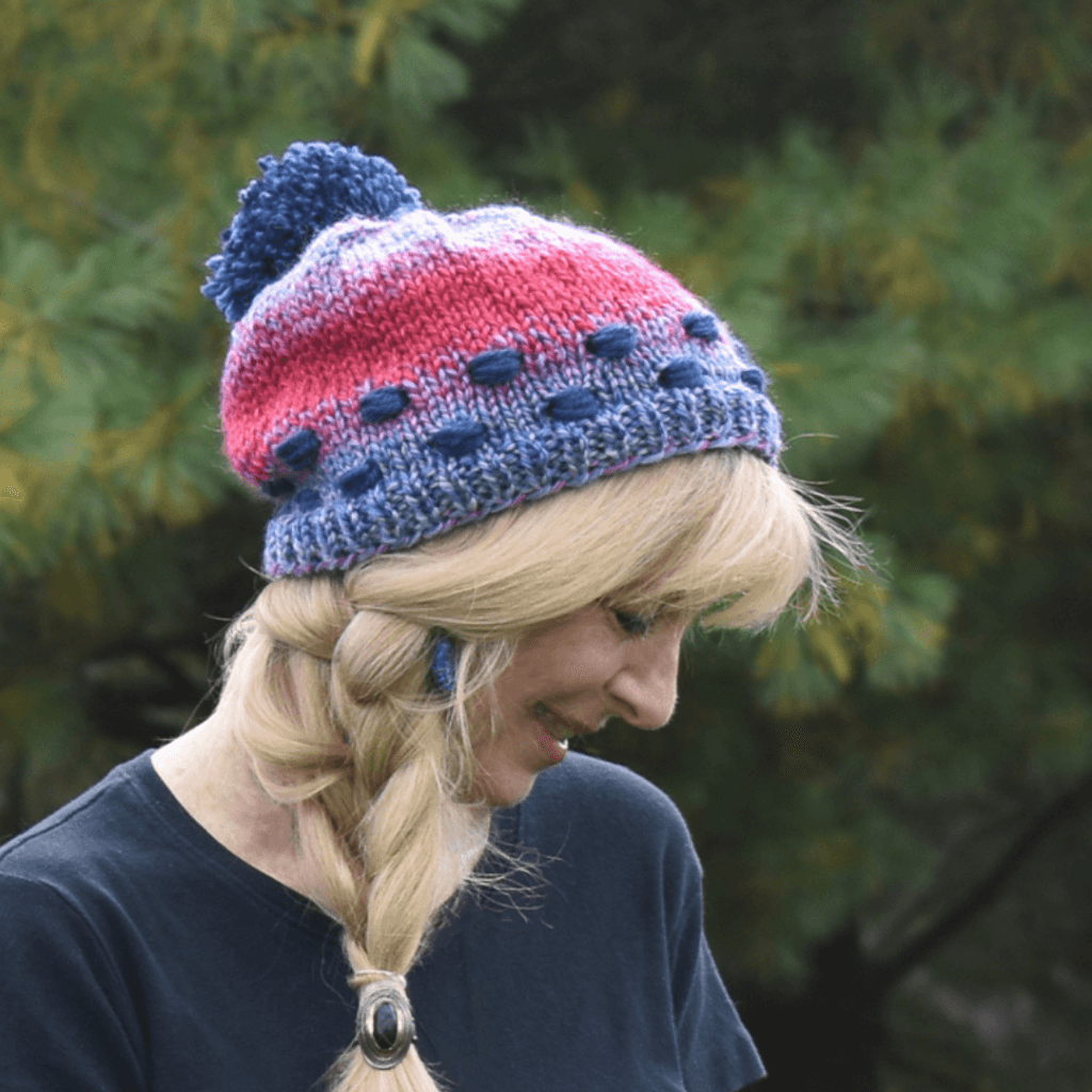 blue and red hat with pompom on blonde woman