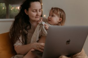 mother with laptop and baby on her lap