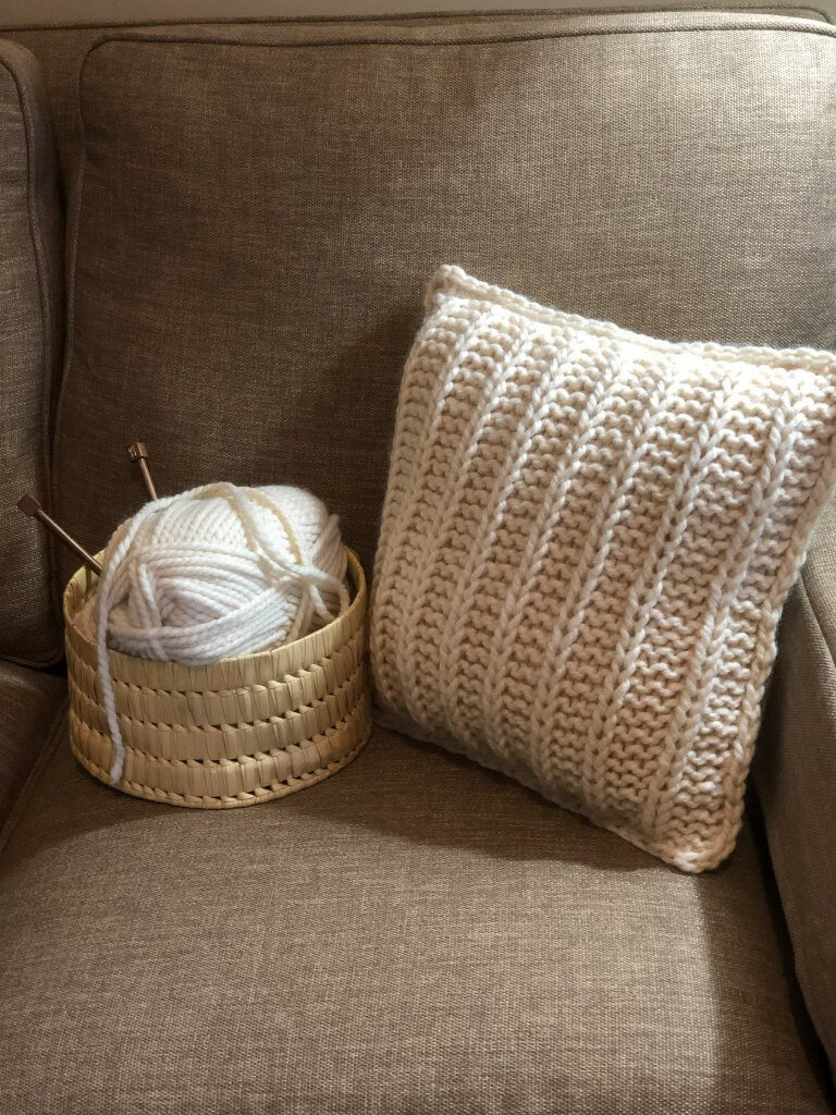 photo of pillow and basket of yarn on sofa