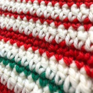 closeup image of red, white and green striped crocheted fabric
