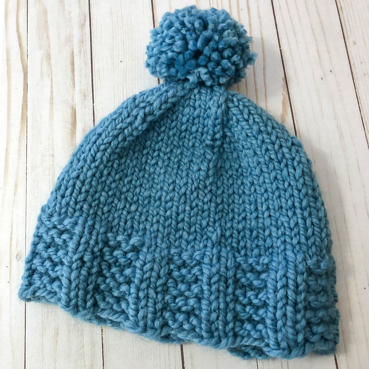 blue knitted hat with pompom, flat lay
