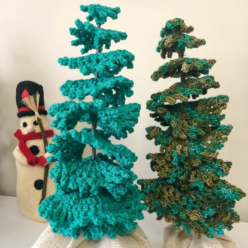 two crocheted trees with felt snowman in background