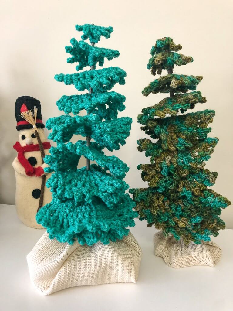 two crocheted trees with a stuffed felt snowman in the background