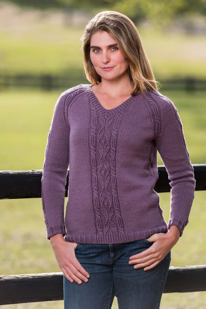 Woman wearing V-neck raglan pullover with front cable detail