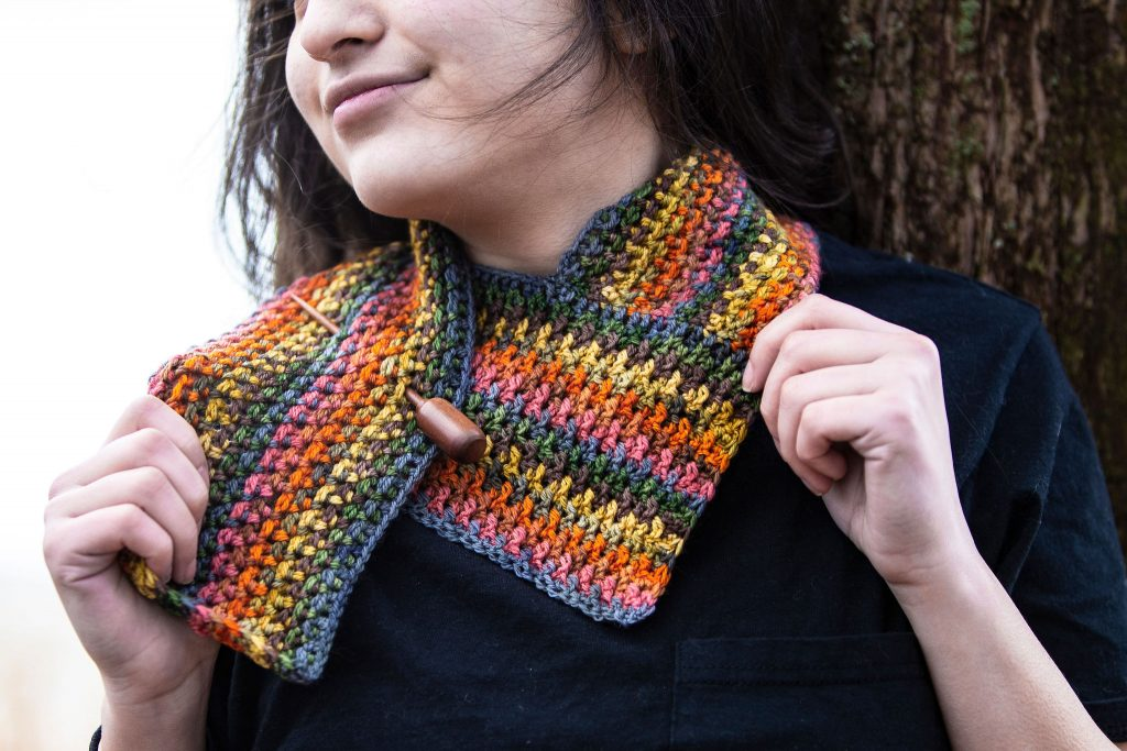 woman wearing colorful crocheted scarf with shawl pin