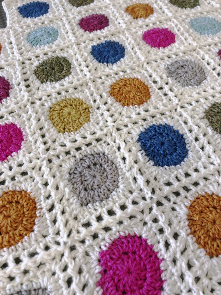 colorful crocheted dots on a white background, closeup of Lollidots Shawl crochet pattern by Edie Eckman