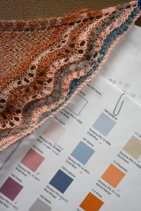 page of color samples and edge of a piece of knitting