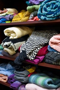 stacks of folded sweaters on shelves