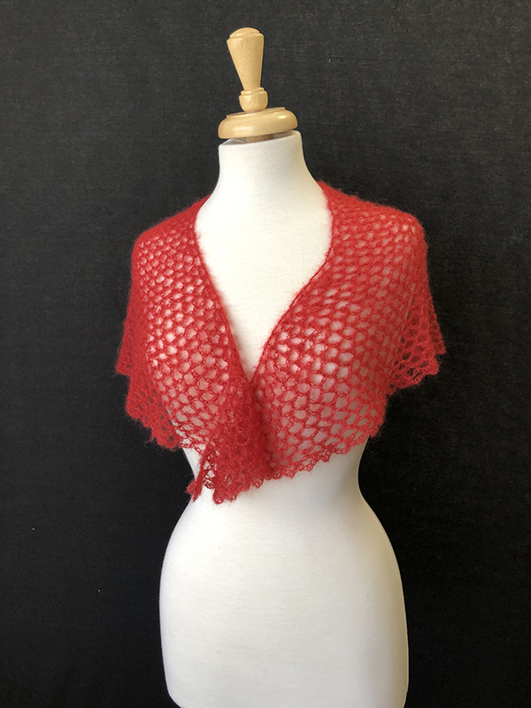 red mesh shaped shawl on white dress form