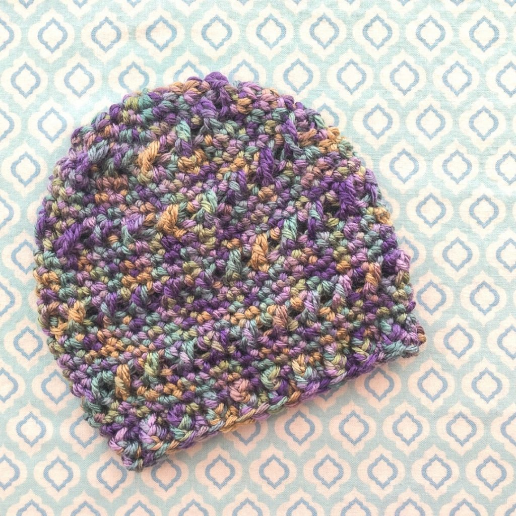 lavendar and green varietgated textured baby hat flat lay on patterned background
