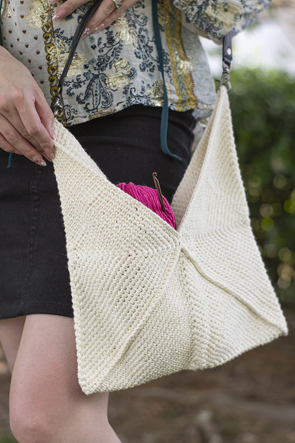 zoomed in photo of white bag made with three folded triangles, with a leather shoulder strap