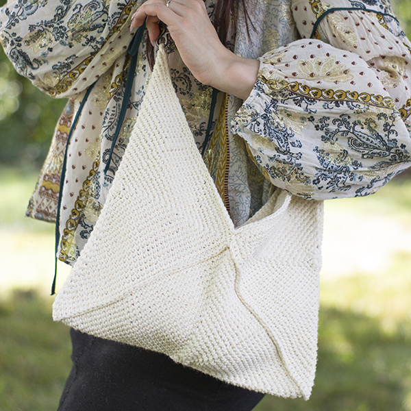 zoomed in photo of white crocheted shoulder bag on woman