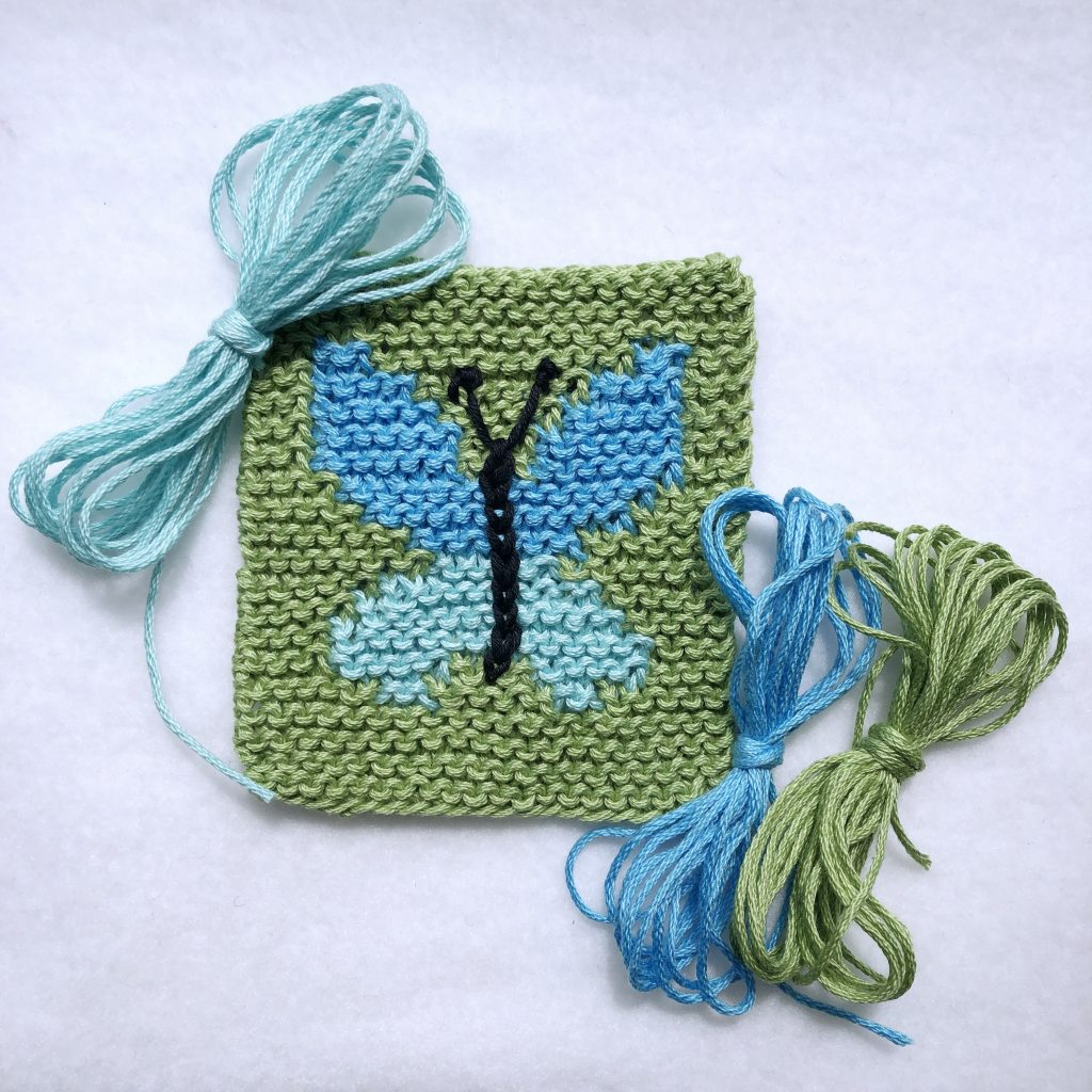 """square garter stitch coaster with blue intarsia butterfly knit into the center, shown with three yarn """"butterflies"""""""