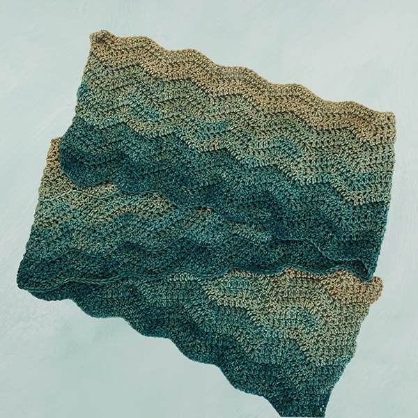 flat lay of ripple scarf in shades of sage green