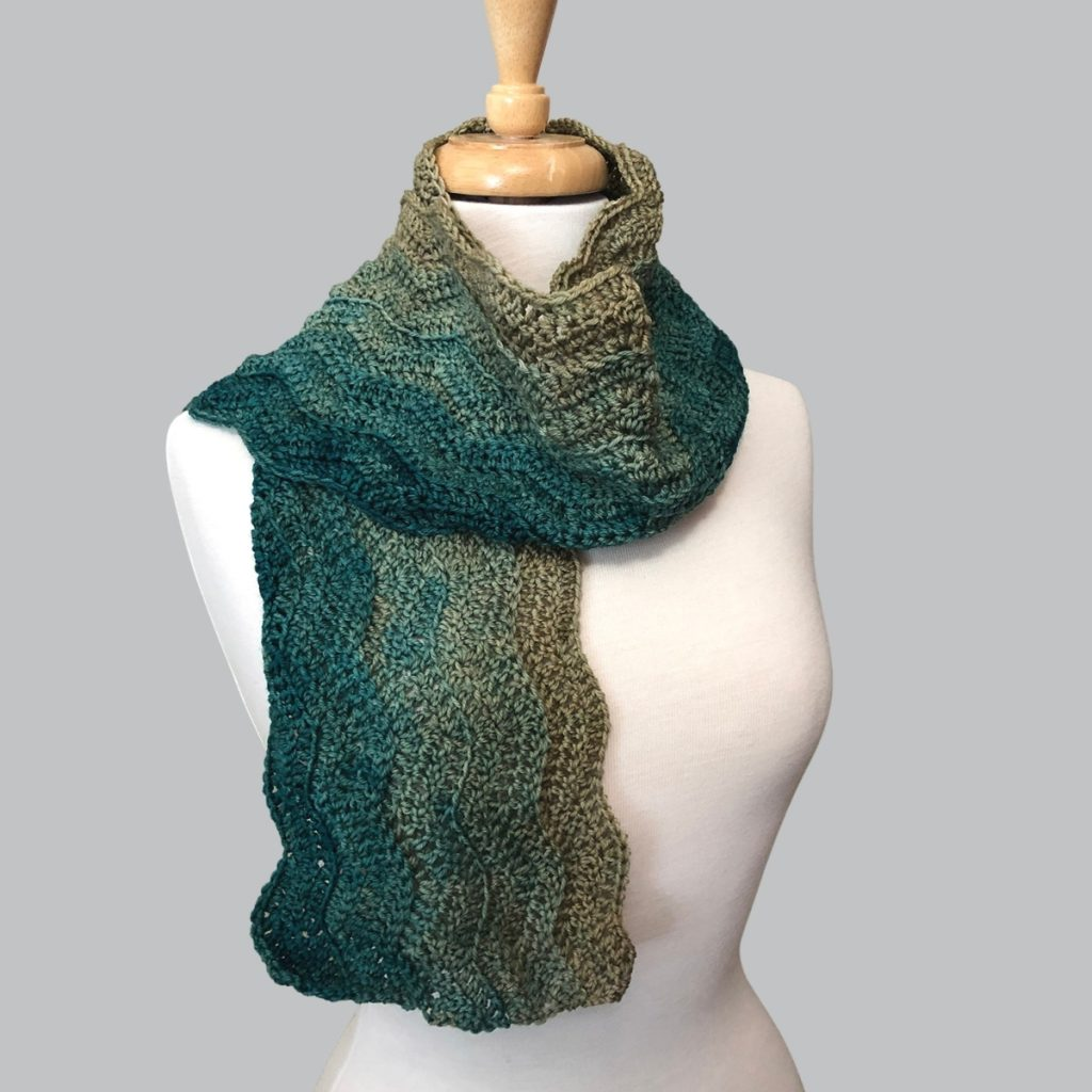 ripple scarf in graduated shades of sage green wrapped around the neck of an off-white dress form