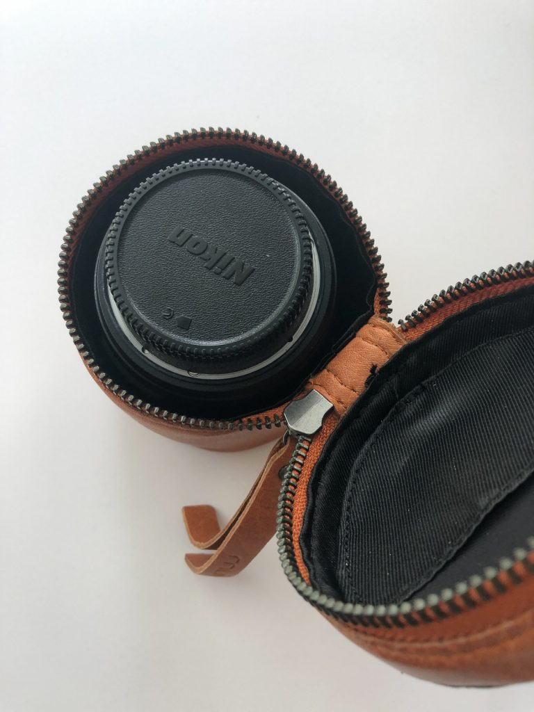 open cylindrical leather box with camera lens inside
