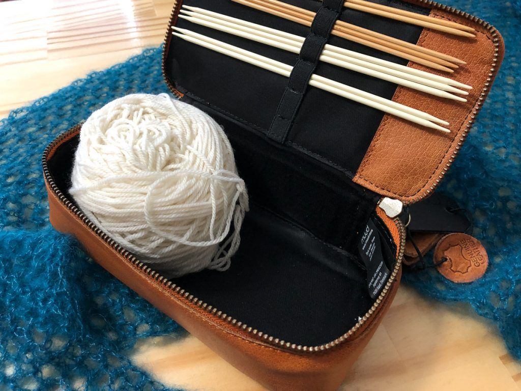 open rectangular leather box holding a white ball of yarn, with double pointed needles in top of box