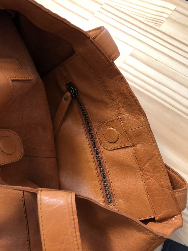 inside of leather bag showing zippered inside pocket and magnetic closure