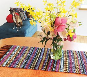 colorful table runner under a vase of flowers