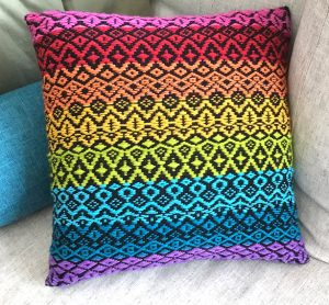 bright patterned woven pillow in crayon colors