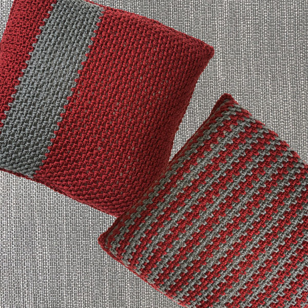 two grey and dark red pillows-one with narrow stripes and one with a single wide grey stripe