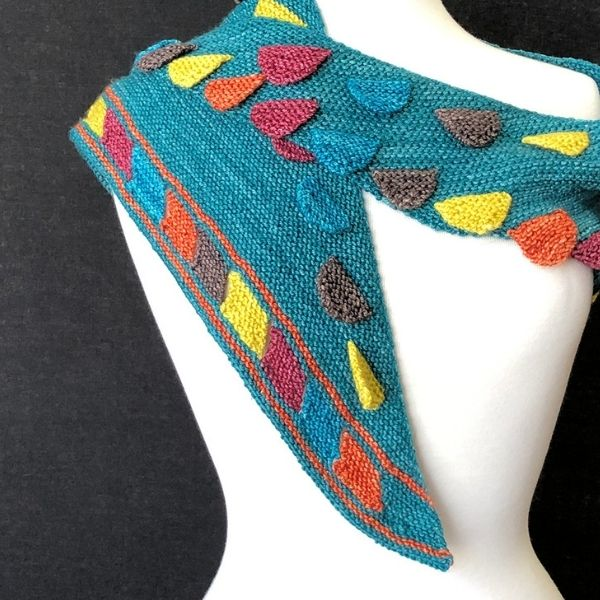 teal shawl on shoulders of dress form, colorful tabs and instarsia work detail