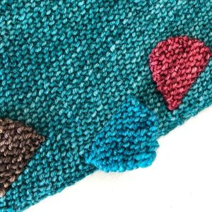 close up view of colorful garter stitch tabs on teal garter stitch background