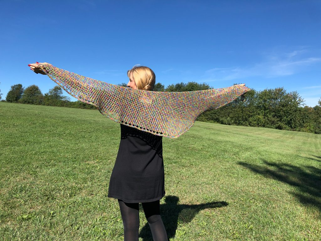 woman holding Rosemorran Shawl out in wingspan view, standing in a grassy field with a blue sky